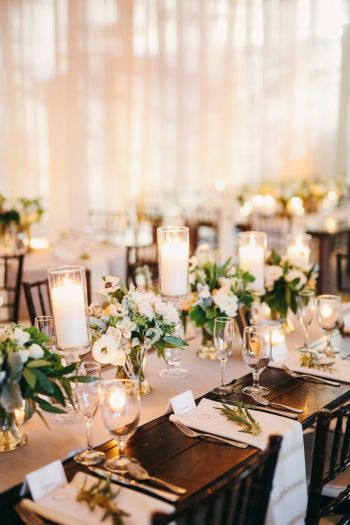 Napa tabled lined with small arrangements and candles. Olive branch on each napkin. Spring wedding in Las Vegas by Layers of Lovely Floral Design and Gideon Photography.