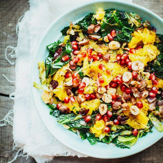 Colorful warm salad with kale, brussel sprouts, pomegranate and hazelnuts. Healthy and super tasty and the same time. Perfect for fall.