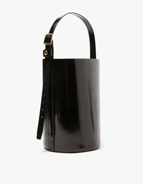From Trademark, a structured leather bucket bag in Black with minimalist styling. Features single adjustable shoulder strap, pressed front logo, flat bottom and gold tone hardware.   •	Leather bucket bag in Black •	Single adjustable shoulder strap •	G