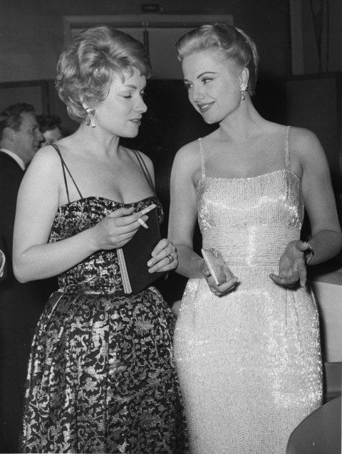 West German actress Ruth Leuwerik, smoking a cigarette, left, is pictured with American actress Martha Hyer in 1960.