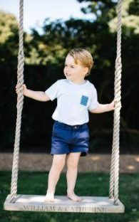 Prince George standing barefoot on a swing in the grounds of Anmer Hall