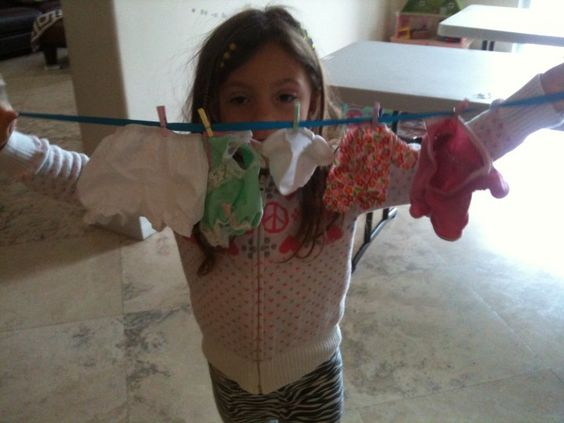 Excellent bilateral coordination activity...Hanging up doll clothing on a ribbon with mini pins!