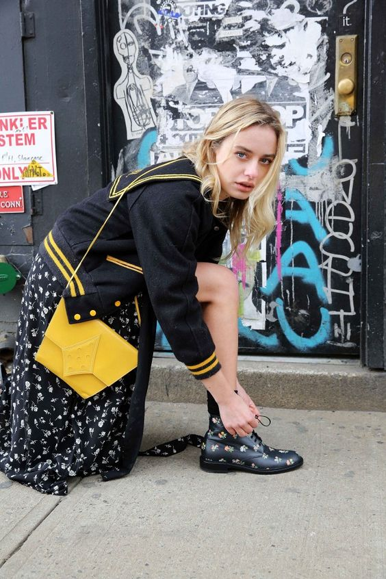 Sonya Esman wears a varsity jacket with a yellow bag over a slit maxi dress with floral boots