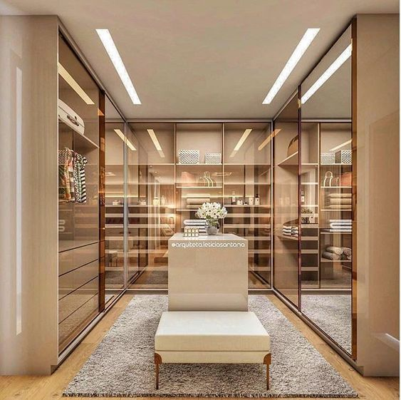 contemporary walk-in closet with glass doors, chairs and island table #glass #cabinets #closet #storage #organization #allenrothCloset #allenAndRothCloset #closetShelves