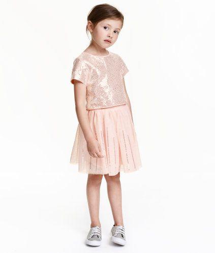 Lichtroze. Een set bestaande uit een korte blouse en een tulen rok die bezet zijn met pailletten. De blouse is van geweven kwaliteit en heeft korte mouwen