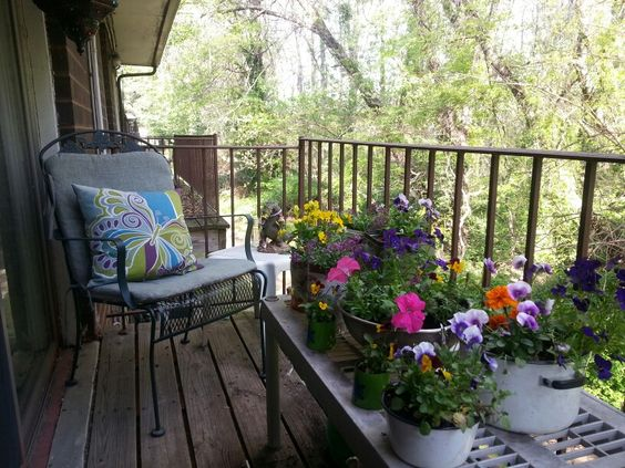 Brighten up a boring balcony with colorful flowers. Use upcycled pots, pans, and tins as planters for a fun & rustic look.