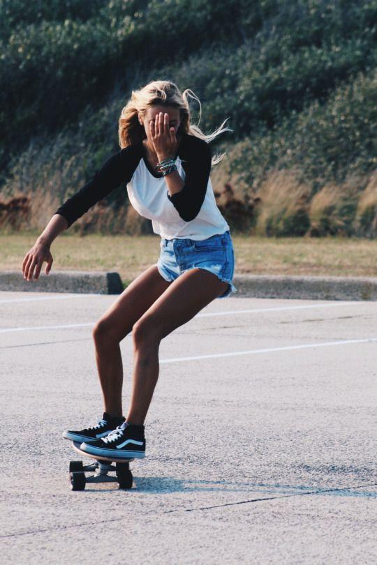 両足を乗せてスケートボードで走る女性