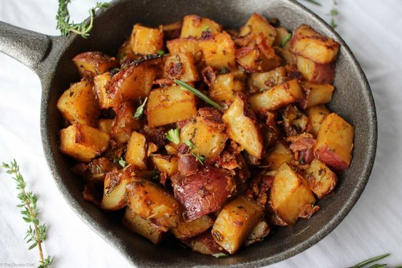 Oven Roasted Breakfast Potatoes - Perfectly seasoned and roasted potatoes topped with caramelized onions, bacon pieces and fresh herbs. The perfect side dish for breakfast!