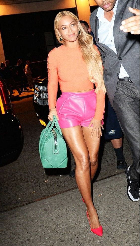 Beyoncé wears an orange crop top, pink leather shorts, neon pink pointed-toe pumps, and a green Givenchy bag