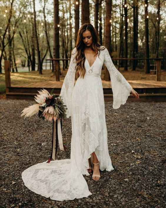 A High Low Boho Lace Wedding Dress With A Deep Neckline Bell Sleeves And A Train Wedding Dress Long Sleeve Wedding Dresses Lace Aline Wedding Dress