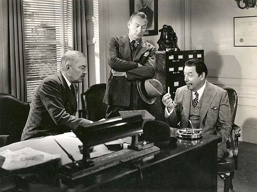 "Charlie Chan explains to Inspector Regan how a police detective's cigarette that has ""died in infancy"" suggests that a very difficult case is at hand. Publicity Still from Charlie Chan at the Opera (1936)"