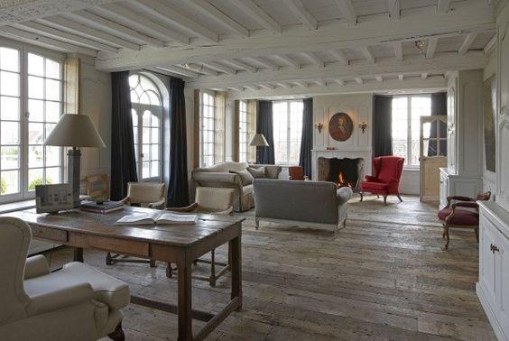 Een grote, heldere woonruimte op de gelijkvloerse verdieping, vol vensters die uitkijken op het landschap.
