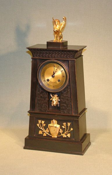 """A French Empire bronze & ormolu clock in the Egyptian style with 8 day silk-suspension striking movement by Hemon a Paris, also marked """"Ledure Bronzier"""", enclosed in bronze obelisk tower decorated with hieroglyphics & mounted with recessed bull's head & stylised Egyptian figure with flowers, surmounted by winged sphinx. (See: French Bronze Clocks by Elke Niehuser page 7). Circa: 1820 Ref: 5325"""