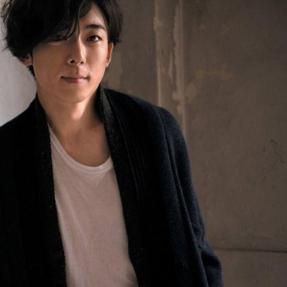 白いシャツに黒いジャケットを着て微笑んでいる高橋一生の画像