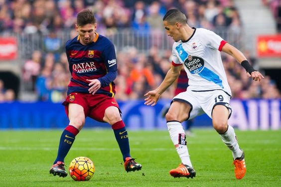 Lionel Messi of FC Barcelona and Faycal Fajr of RC Deportivo La Coruna compete for the ball during the La Liga match between FC Barcelona and RC Deportivo La Coruna at Camp Nou on December 12, 2015 in Barcelona, Catalonia.