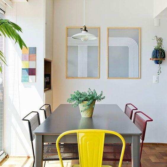 WEBSTA @ historiasdecasa - adoramos o jeito como a arquiteta @renataleite combinou, ou melhor,  descombinou as cadeiras na sala de jantar (que aliás fica na varanda pra otimizar espaço): quatro modelos iguais, duas cores diferentes e uma Tolix amarela para coroar ♥ na parede, os pôsteres são da marca do marido dela, a @diferentesmentes e o vaso foi comprado na lua de mel dos dois... muito amor né? #decoração #todacasatemumahistoria #varandaintegrada #casacolorida #tolix…