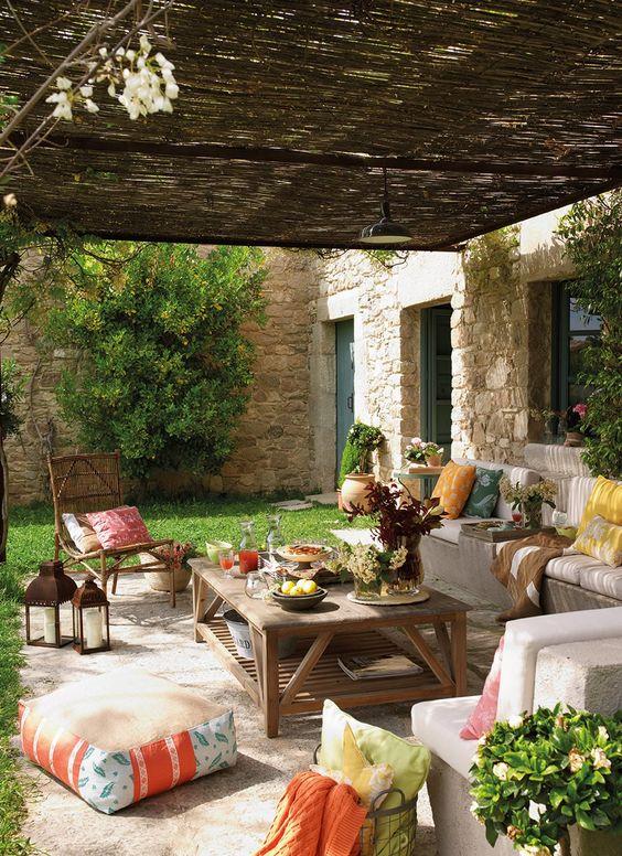 Disfrutar del porche  Mesa de centro de madera y cesto con cojines de Sacum. Puf en el suelo de L'Atelier des Cousines. Flores de Jardiland....