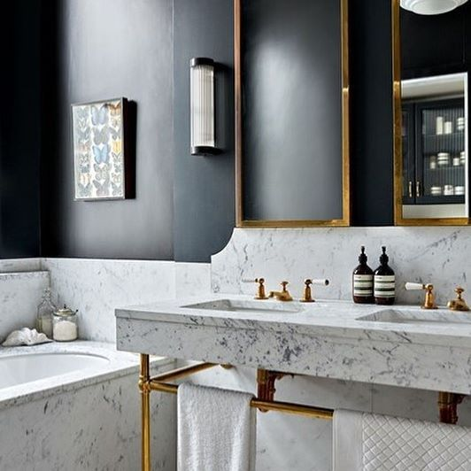 This deep blue-black paint color adds the perfect depth to this marble bathroom outfitted with brass accents designed by @hackettholland @houseandgardenuk #bathroom #inspo