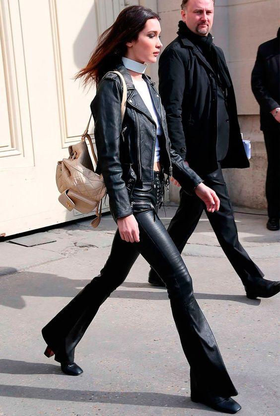 Street style look Bella Hadidi com jaqueta couro, calça resinada, botas e white choker.