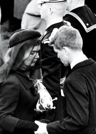 Jackie guided by Bobby Kennedy after President Kennedy's burial, at Arlington National Cemetery; she is holding the American flag that covered his coffin.