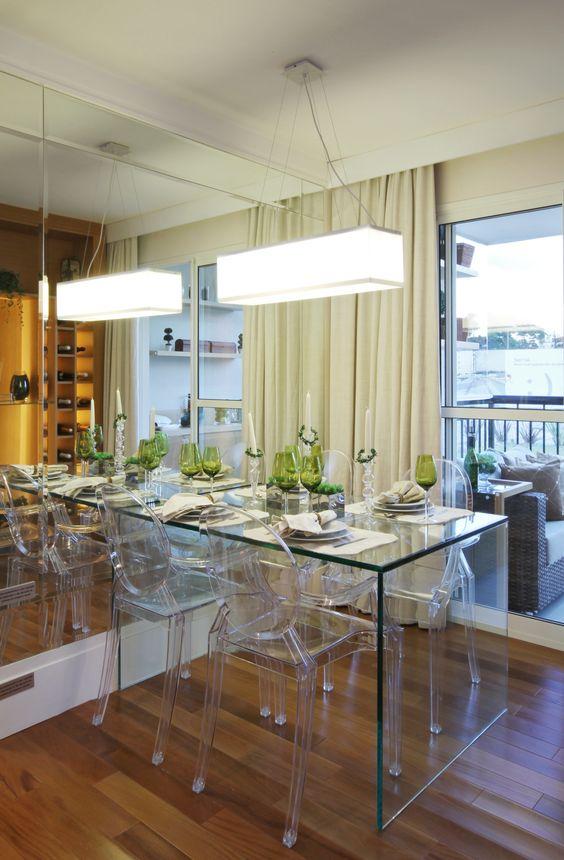 """A mesa em vidro e as cadeiras em acrílico incolor deixam a sala de jantar sofisticada e com um ar """"clean"""". Agregadas à parede revestida em espelho, parecem ampliar o ambiente http://ow.ly/blR6H:"""