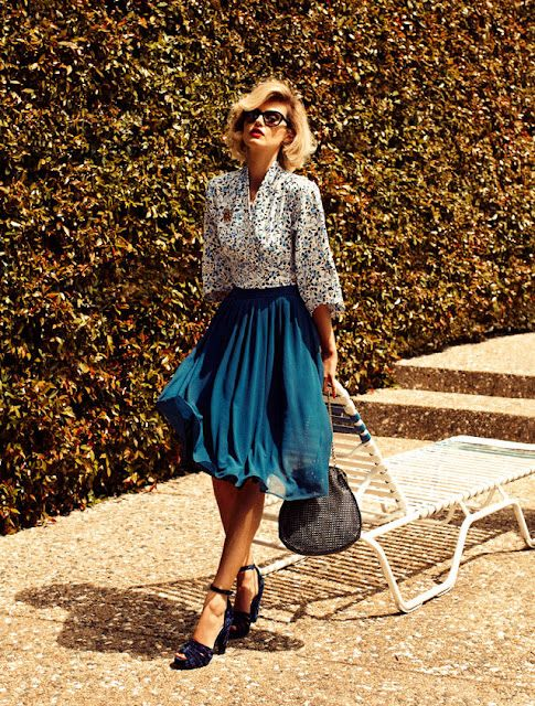 Blue Skirt flowing pleated ankle wrap black sandals black wrist bag blouse with small white and blue pattern sunglasses blonde curled hair sunshine lawn chair bushes around the pool
