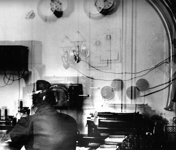 Marconi Room.. MR Harold Bride, sitting at the table, afterwards saved. Two exposures on the one plate! This is the only photo ever taken of the Marconi Room of the Titanic. Passenger Father Browne....