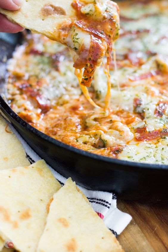 Craving pizza but want something new? Check out this extra cheesy pepperoni pizza dip with thin crust chips for dipping all the cheesy goodness! Extra Cheesy Pepperoni Pizza Skillet Dip with think crust crackers Recipe | Take Two Tapas