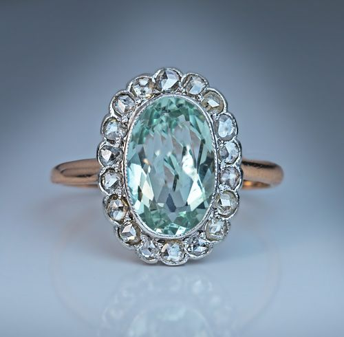 A Vintage Aquamarine and Diamond Cluster Ring, Circa 1915. The platinum topped 14K rose gold ring is bezel-set with an oval aquamarine framed by 18 old rose cut diamonds.