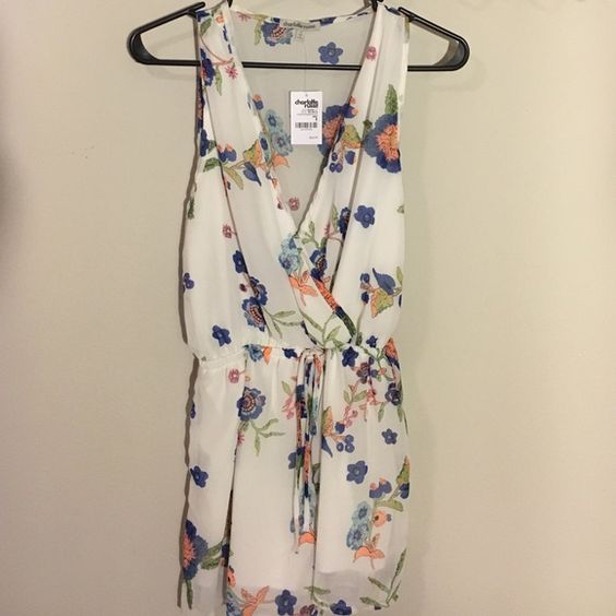 White/eggshell romper with floral detailing! This adorable romper has never been worn! It's a thin mesh-y material that's between white and eggshell and has blue, orange, and green floral patterns. Has a built-in belt for a cinched waist! Charlotte Russe Dresses