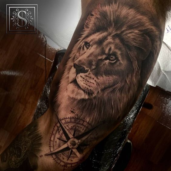 Black and grey style lion tattoo on the right inner arm.