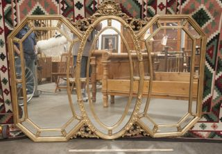 EXTRA LARGE 3-SECTION MIRROR IN A GOLD PAINTED WOOD FRAME WITH CARVED DETAILS.