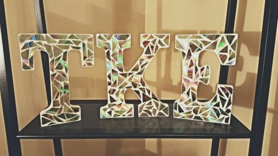 Wooden TKE letters made with cut CDs