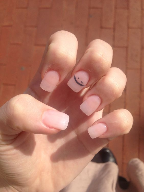 clear pink gel polish with black wink on the middle finger.
