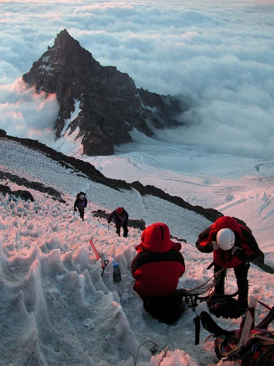 view above clouds (Climbers on Ingraham Glacier, above Little Tahoma. Mount Rainier is a massive stratovolcano located 54 miles (87 km) southeast of Seattle in the state of Washington, United States.)