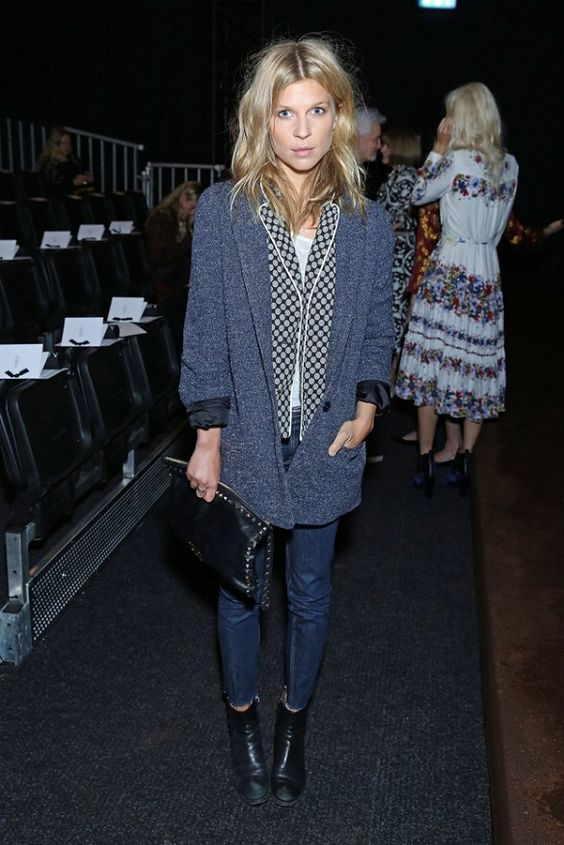 Clemence Poesy wears a t-shirt, printed pajama style top, blazer, skinny jeans, boots, and a Valentino clutch: