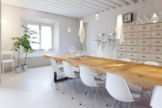 White room, long wood dining room table, white eames chairs