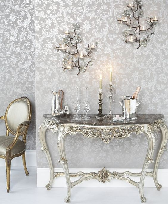 Console table, £445, Sweetpea and Willow. Silver jug, £90, Cox and Cox. Silver fruit, £3 each, Bhs. Champagne flutes, £12 each, John Lewis. Water glasses, £21 each, wine glasses, £20 each, Armani Casa. Rococo wallpaper from The Charlie Wilson Collection, £48/10m roll, Cole and Son. Wall Sconce, £49 each, Graham and Green. Chair £289, Velvet Store. Pewter candlestick holder, £15, Debenhams. Long candlestick holder,  £20, Bhs. Candles, £10 for 6, www.truegrace.co.uk.