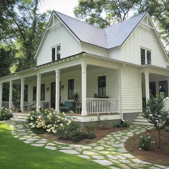 White farmhouse with porch, and flagstone path.