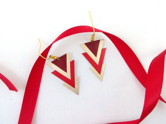 Les boucles doreilles sont composées de triangles de taille et de couleur différente, dorés, bordeaux, et rouges. Les triangles sont fabriqués à partir