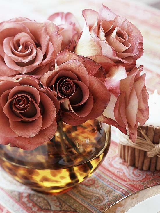 Candles and roses are perfect elegant touches for your holiday table. Roses look majestic in low bowls with amber-colored water. Wrap candles in cinnamon sticks to enjoy a splendid autumn aroma.