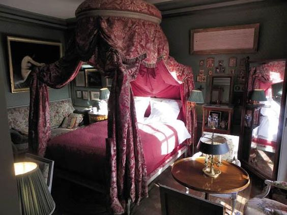 Room of the Day ~ Madame Bovary could have slept here.  Cranberry Polonnaise bed, dark walls, standing mirror, settee, round table with dark shade lamp - Jacques Garcia ~ bedroom in his chateau 4.6.2014