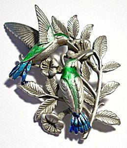 Pewter humming birds hand enameled brooch or pin. It is an unusual piece, measuring approximately 1 1/2 by 2 1/8 inches and is in excellent condition. It has 'JJ' manufacturer's markings and a regular locking pin attachment connected to the back. Interesting and rare piece for costume jewelry or hummingbird collectors! $6.50 Priority Mail or $4.50 First Class mail shipping and insurance charge for this item in the U.S.  Price is $29.50.