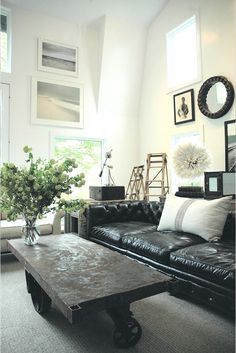 Make that table.  Industrial Style living room with black leather sofa and wal art collection decor