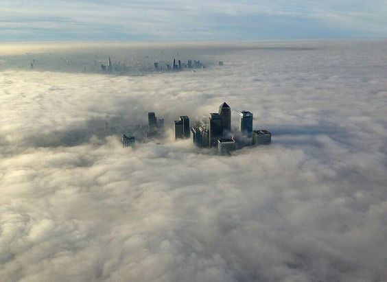俯瞰伦敦市区,金丝雀码头商业区的高楼耸立在云雾之中,英国。拥有多座摩天大楼的金丝雀码头是近年来新兴的金融商圈,230米高的苍鹭大厦(Heron Tower)是目前伦敦最高的建筑。