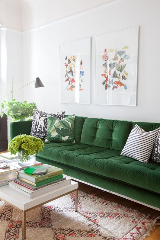 this gorgeous green couch is a stand out in this bright white living room.: