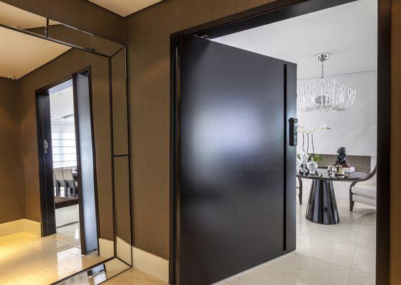 Hall social super elegante com papel de parede da Papercom e espelho como peça de família. A porta blindada laqueada em preto fosco foi projetada especialmente para o cliente.