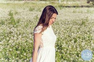 Fotos de chica posando en el campo con flores blancas y vestido