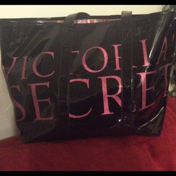 """Victoria's Secret Tote black patent leather & pink Rare and stunning 2009 limited edition VS Tote.  Victoria's Secret in Bold and shimmering pink lettering on shiny black patent leather.  Handle drop of about 9"""". Previously loved and in good condition, no rips or tares.  As with patent leather there are some small scuff marks on back and front mostly a lighter shade of black; thus making them difficult to show up in pictures.  And barely there in person.  Inside appears flawless and depicts…"""