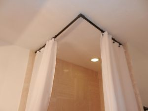 Cheap corner shower curtain rod using painted PVC pipe and hooks in the ceiling